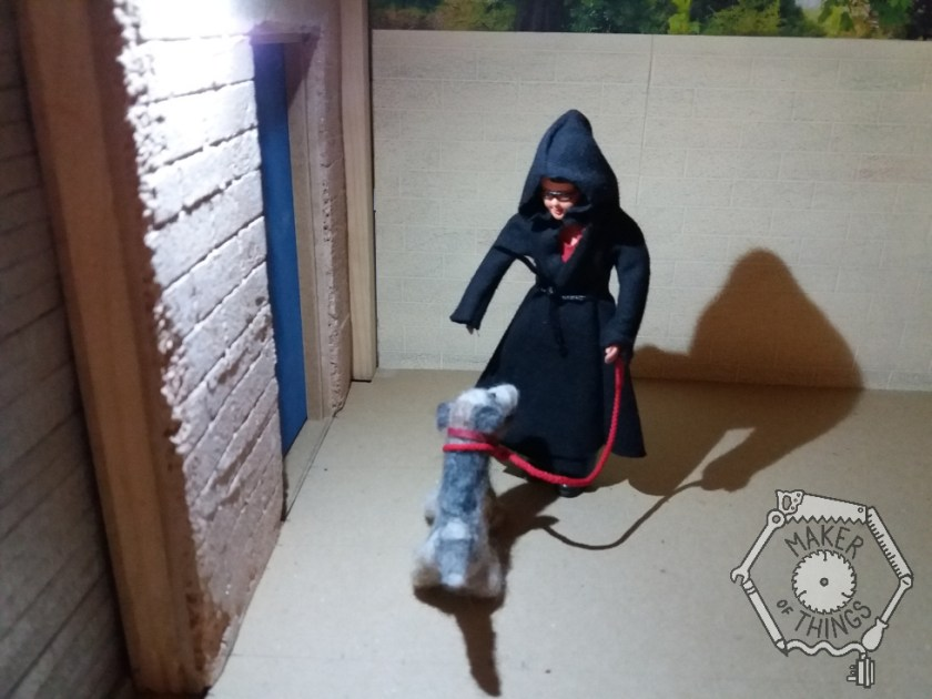 Harriet and Monty Dog are outside the workshop under the floodlight. Monty is on his red lead and Harriet is wearing a big black hooded coat.