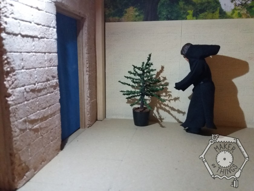 Harriet is under the floodlight outside the workshop door. She has put the Christmas tree in the corner by the door. The tree is small and scrawny, and in a black pot.