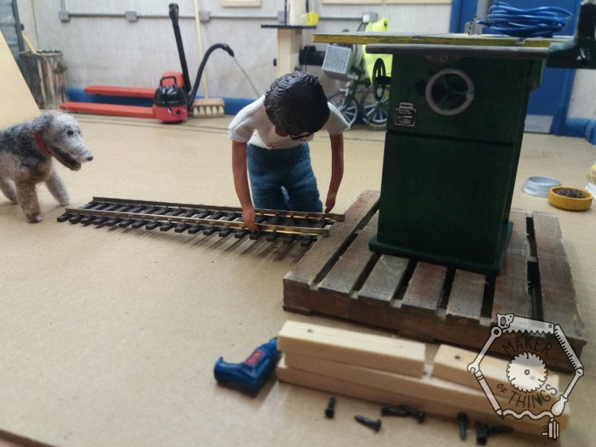 Harriet is placing a length of narrow gauge railway track, with built in sleepers, onto the edge of the pallet as a ramp. The packing timbers are piled up on one side and the blue rope is on top of the table saw.