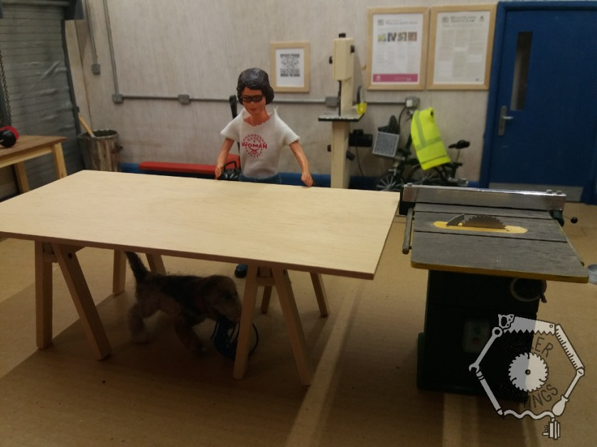 Harriet has placed a pair of saw horses on the floor and put a sheet of eight foot by four foot plywood sheet on top to make a work bench on the out feed end of the table saw.