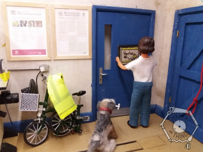 Harriet is standing at the stair door holding the framed embroidery. Monty Dog is looking up at her still holding the hammer. Harriet's bicycle next to the door, and her high viz coat is hanging up on it.