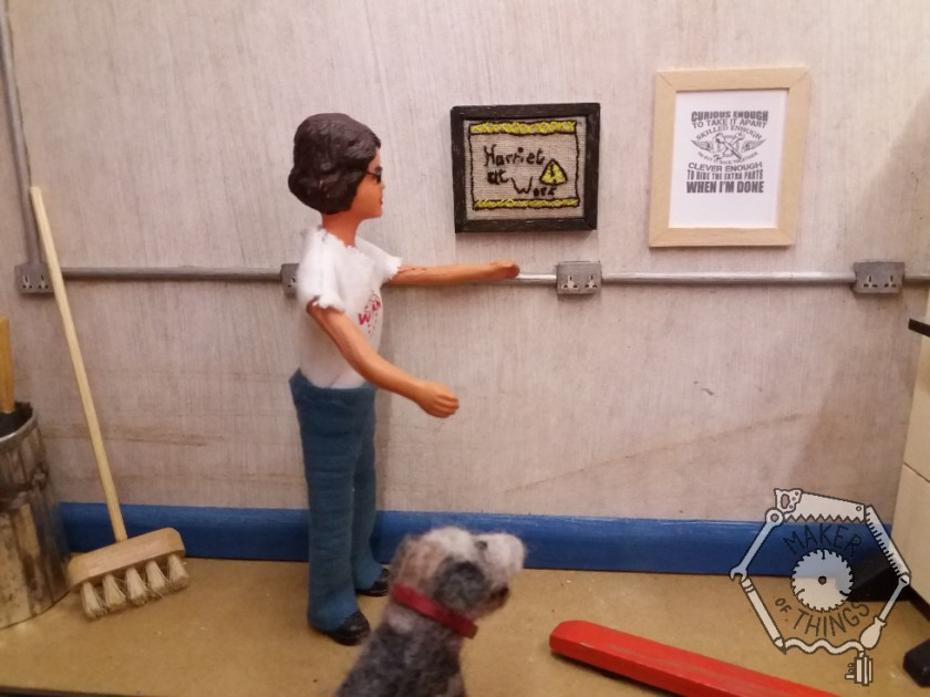 Harriet is standing next to the framed embroidery that is hanging on the wall. Monty Dog is looking at it.