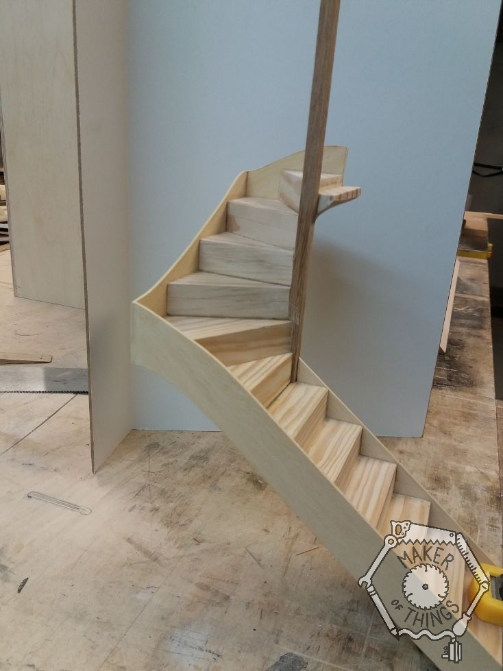 Wall side view of the stairs and winders with a tall newel post fitted, and the stringers on each side of the treads fitted.. The stair is clamped to the edge of the work bench.