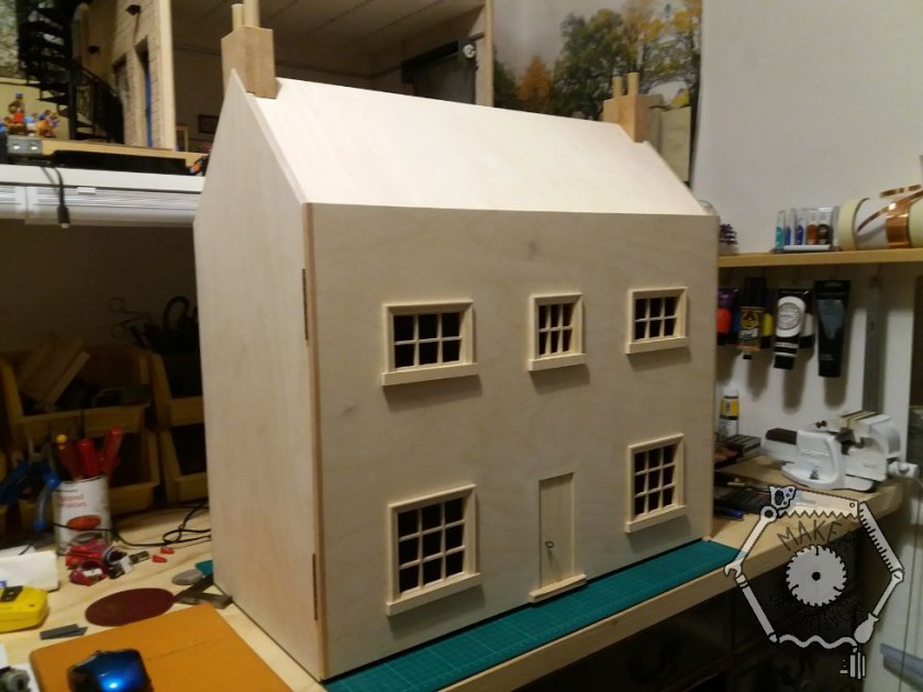 A Georgian style dolls house with a central front door and five windows, a pitched roof with chimneys. In unfinished bare wood.