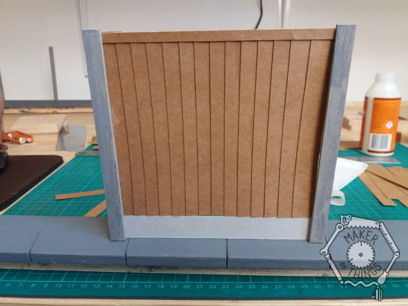 A cardboard fence panel fitted between two of the fence posts with a grey gravel board at the bottom and a trip strip at the top.