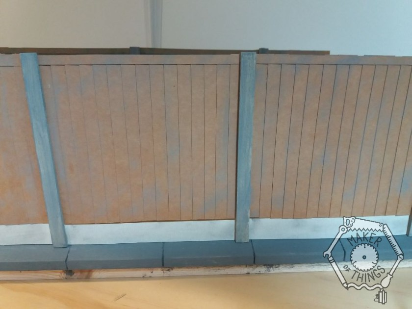 The fence panels in place with some dry brushed grey colour added.