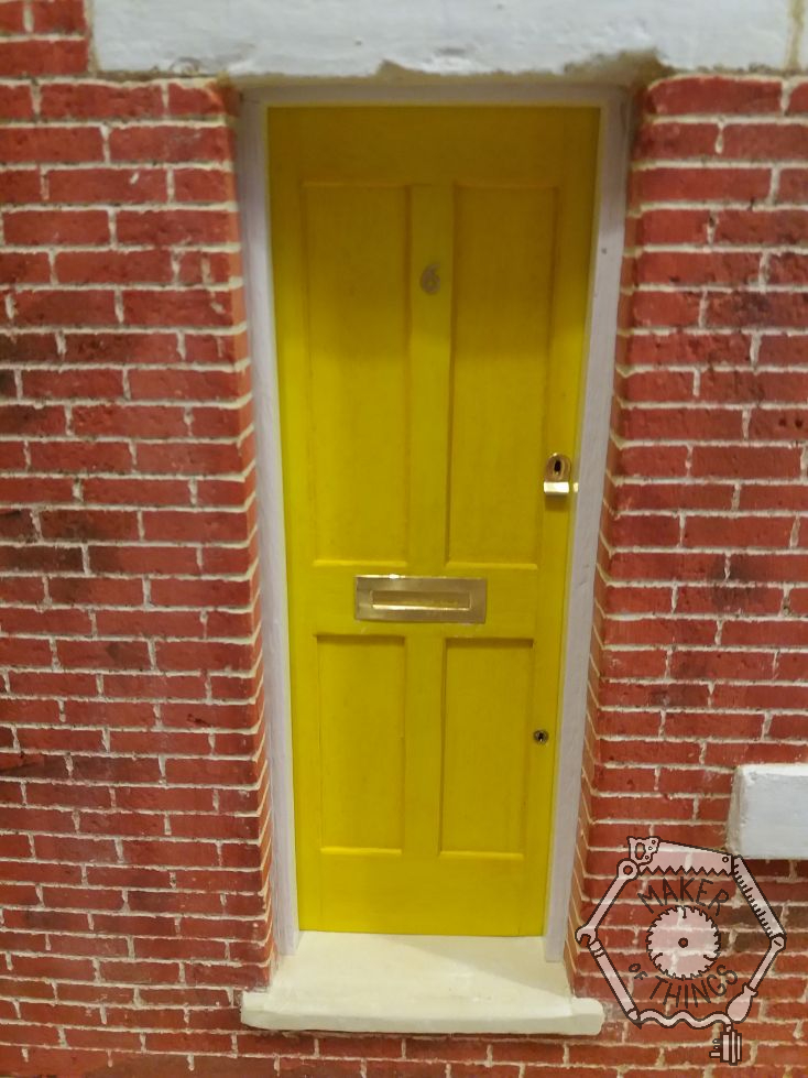The front door in yellow paint with brass letter plate, brass key escutcheons for a rim lock and a mortice lock, and a brass number six.