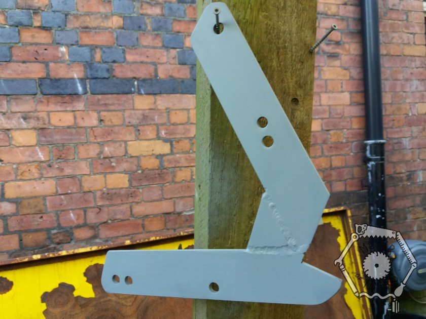 The bracket hanging up having been sprayed with grey primer.