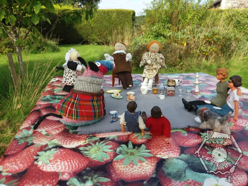 Everyone seated on a blue grey rug, laid on a strawberry patterned oilcloth in the garden having a picnic.
