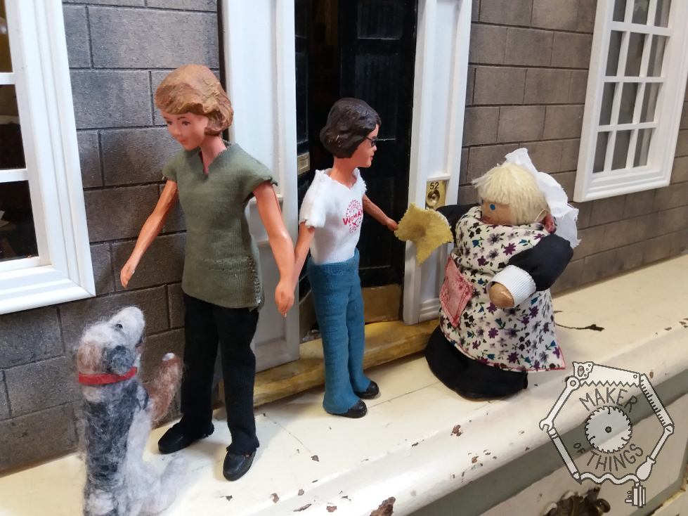 Harriet is still talking to Mrs MacGregor outside the front door. Daisy is holding Harriet's hand and trying to calm Monty Dog as he leaps about excited for a walk.