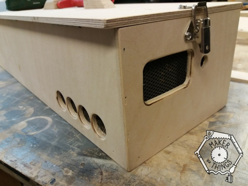 A view of the rear corner of the workstation case showing a rectangular hole, with rounded corners and edges on the end panel, and four round holes on teh back panel.