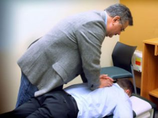 Image of a chiropractor adjusting the back of a patient