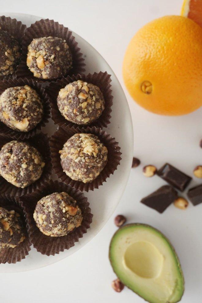 Chocolate Truffles on a plate, an orange, an avocado, chocolate and hazelnuts