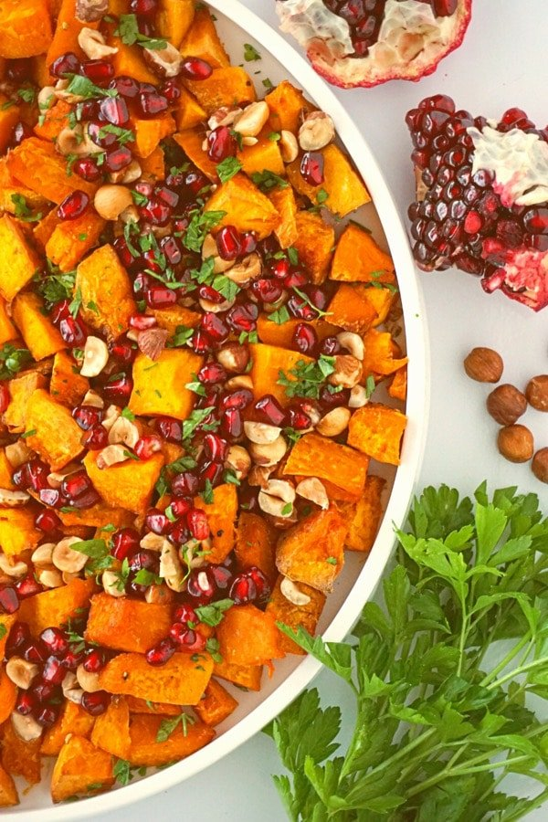Roasted Squash with Hazelnuts and Pomegranate on a white plate