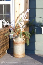 This beautiful arrangement made with a few snowy faux branches and an old vintage milk can makes for the perfect winter porch decor all season long.