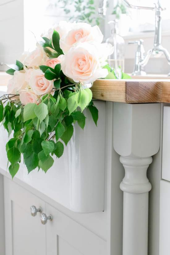 soft pink roses, green leaves, greige cabinetry, grey cabinet, farmhouse sink
