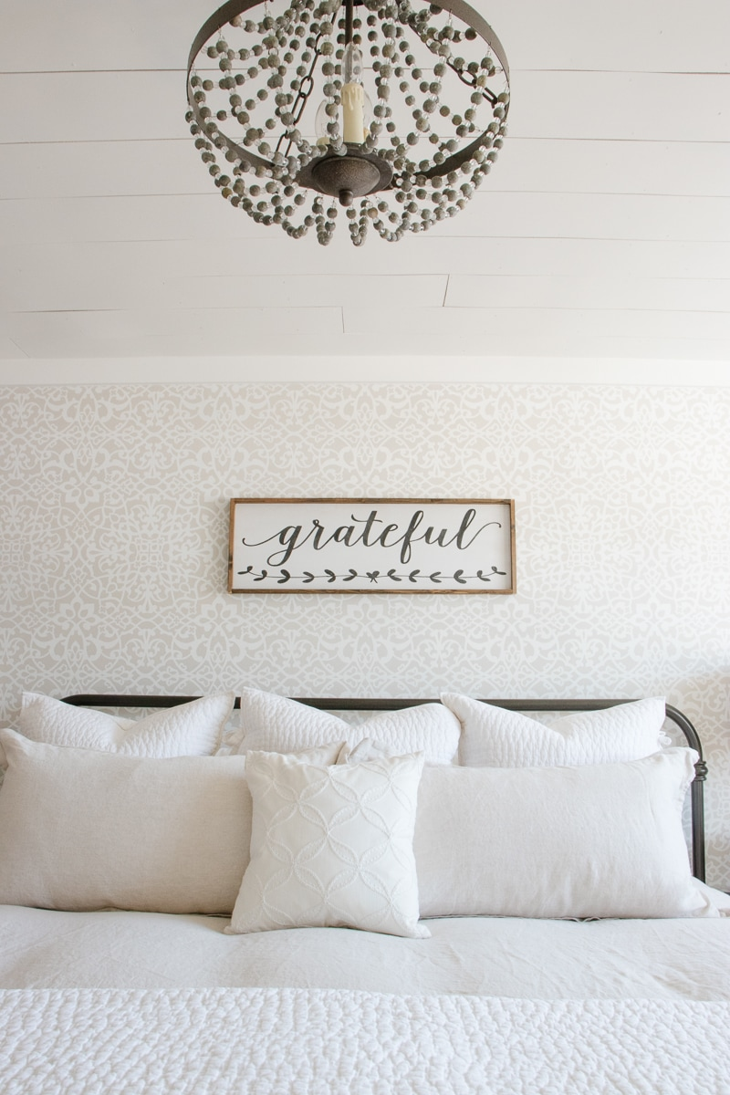 shiplap ceiling, beaded chandelier, linen bedding, stencil wall, wood sign