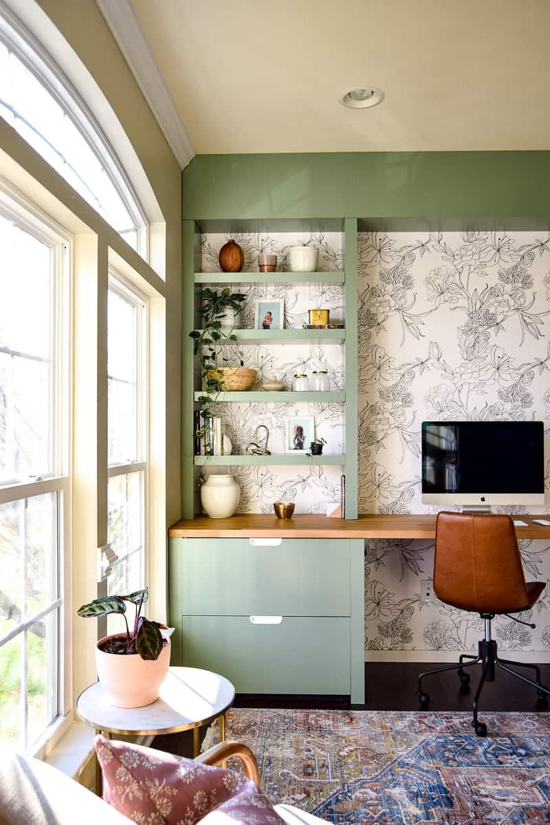 Sharing the big reveal of our formal living room turned modern office space. We used various IKEA pieces, including a butcher block countertop, and Home Depot lumber to make a custom built in desk. We made DIY floating shelves, modern floral wallpaper, and tons of plants to decorate. Modern office ideas | office decor | modern wallpaper | peel and stick wallpaper | one room challenge | DIY office | office renovation | office makeover | office ideas | modern office design | modern office home | home office | modern office space | home decor #oneroomchallenge #modernoffice #officereveal #officemakeover #homedecor #diy