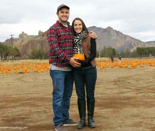 Couple At Pumpkin Patch Holding Pumpkin In Front Of Womans Belly For A Cute Halloween Pregnancy