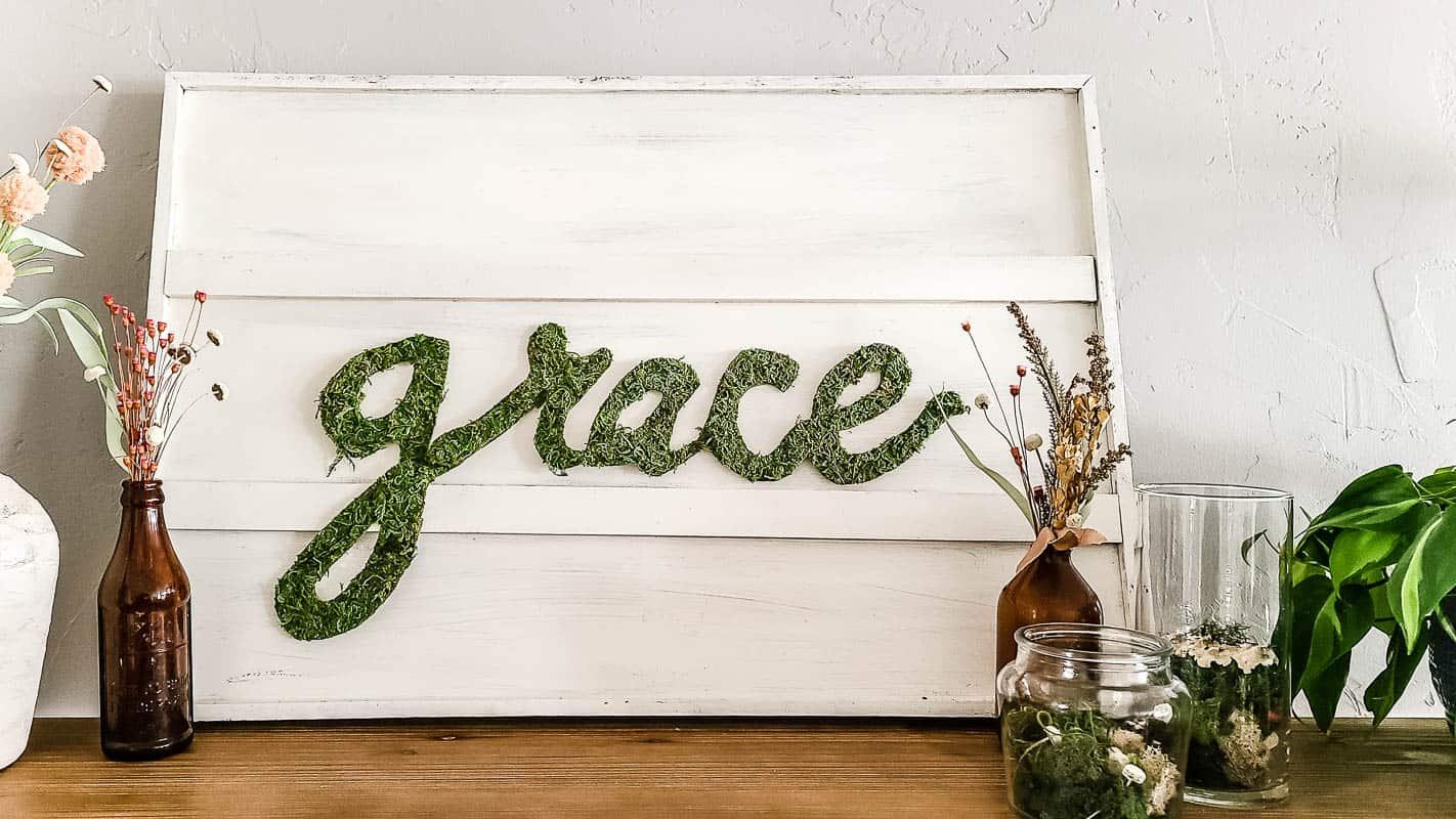 grace moss letters on white sign for spring decorations on living room shelves