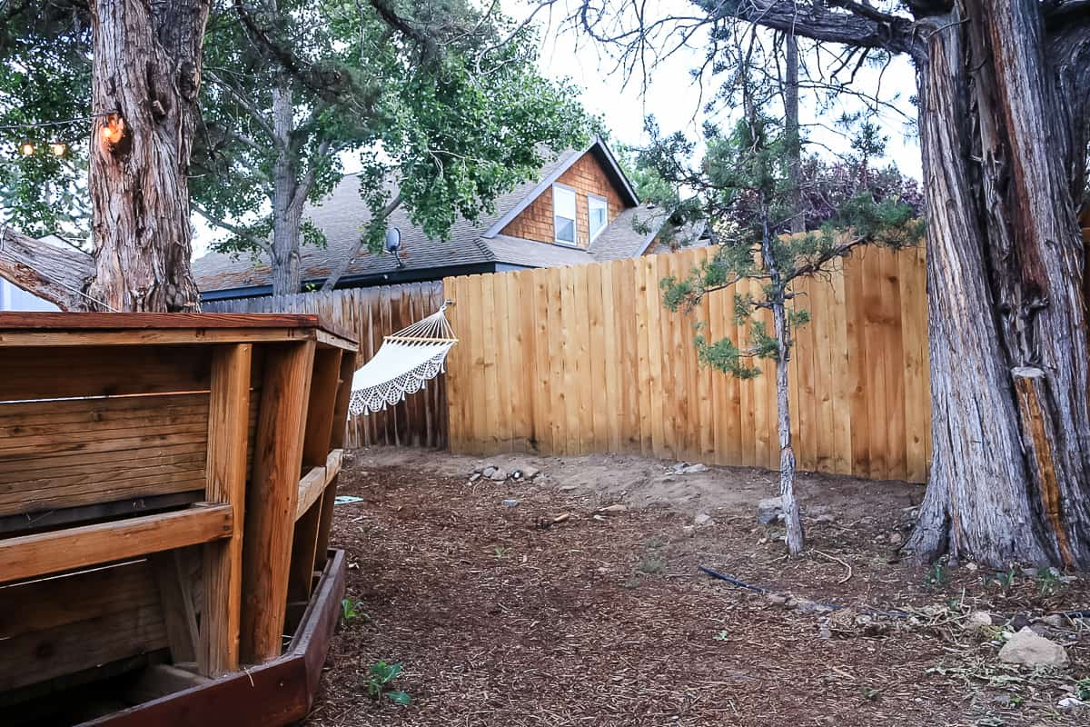 shows a wood fence behind a deck