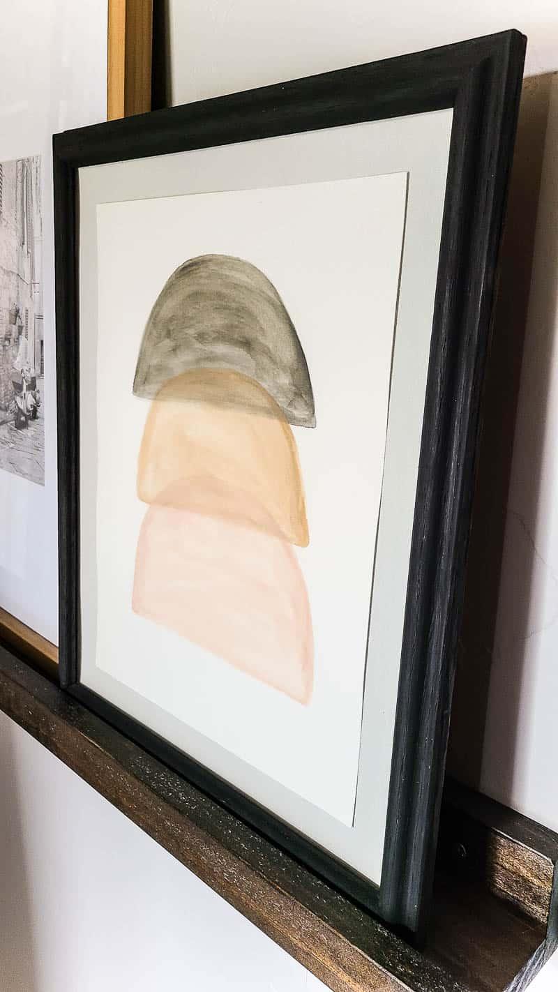 Slight side view of neutral boho wall art on shelves