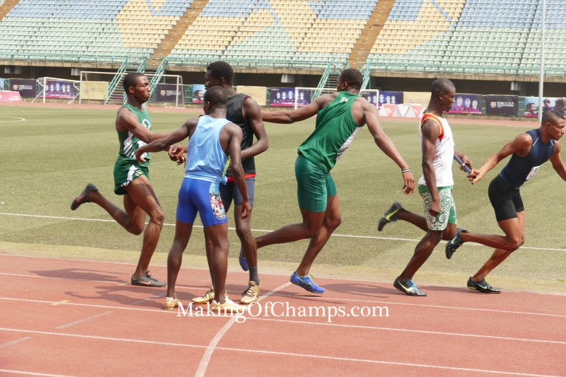 Oguma reaching out to Jakpa and handing him the baton in the 4x200m relay