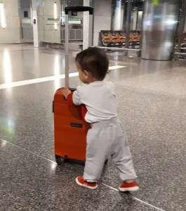 Bebé en aeropuerto llevando la maleta