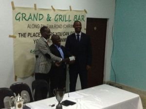 Mbatila (Middle) presenting the cheque