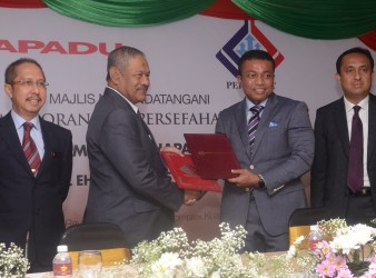 Abdul Aziz Ibrahim (left) and Shafiz Shahrani exchanged documents after the MoU ws signed today.