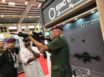 Chief of MAF General Tan Sri Raja Mohamed Affendi trying a weaponry system at the EDIC Caracal UAE booth