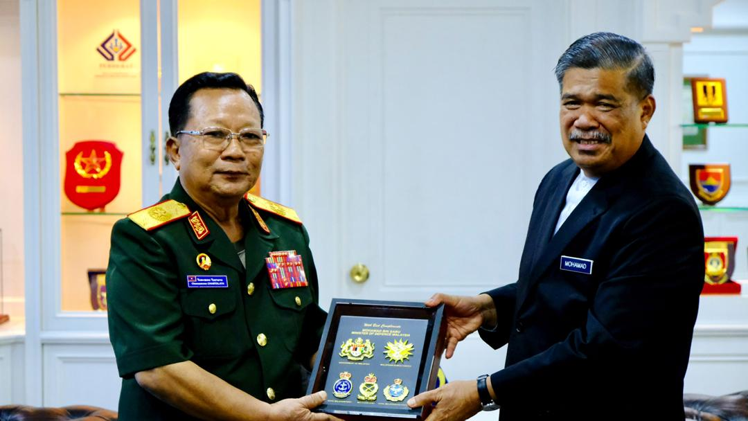 Mohamad Sabu right exchanging momento with General Chansamone after signing the MoU on greater bilateral defence cooperation in Kuala Lumpur on Friday.