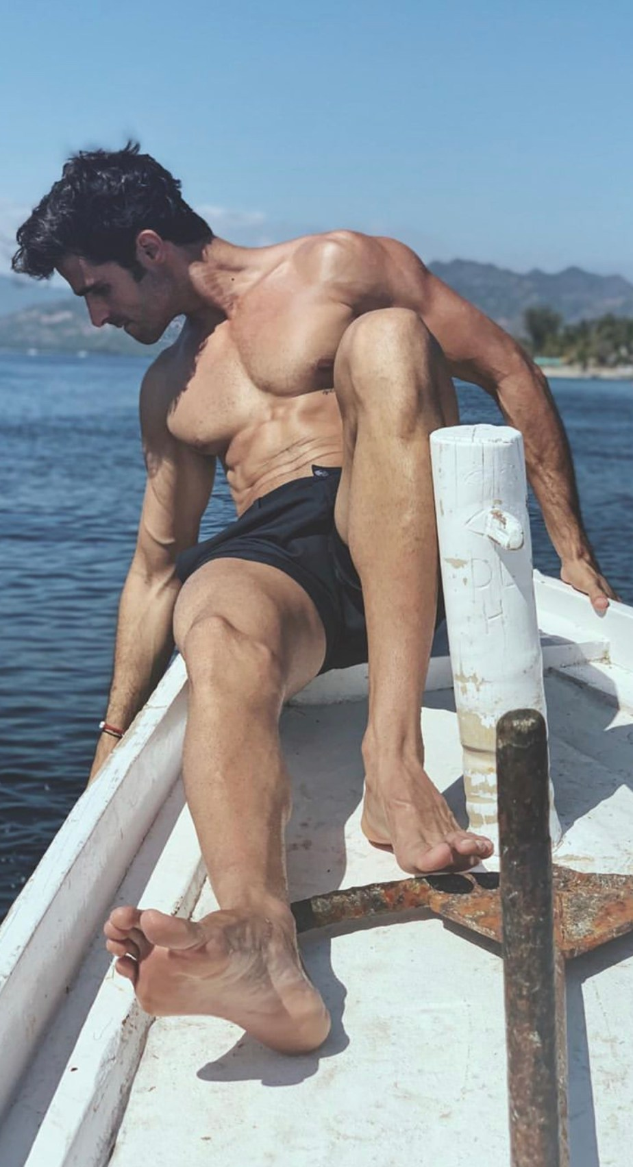 juanbetancourtt shirtless with his bare size 11 soles on show on a boat