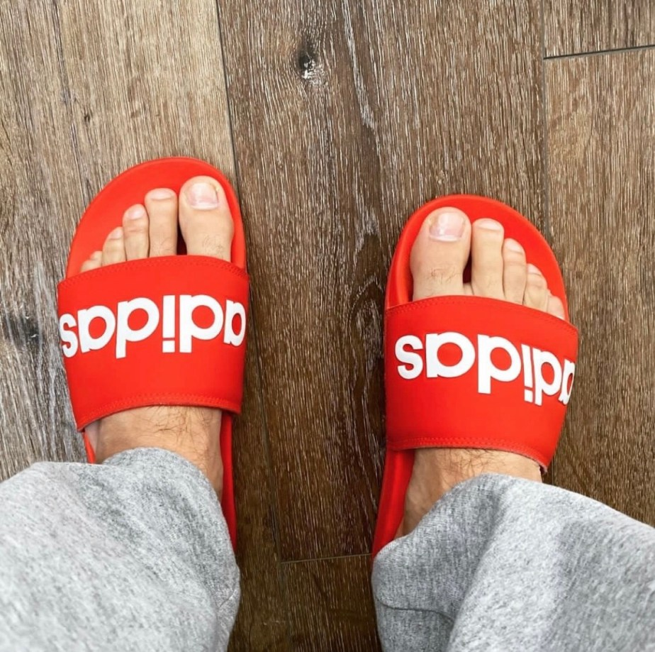 takeuhwhiff's bare feet in red Adidas slides