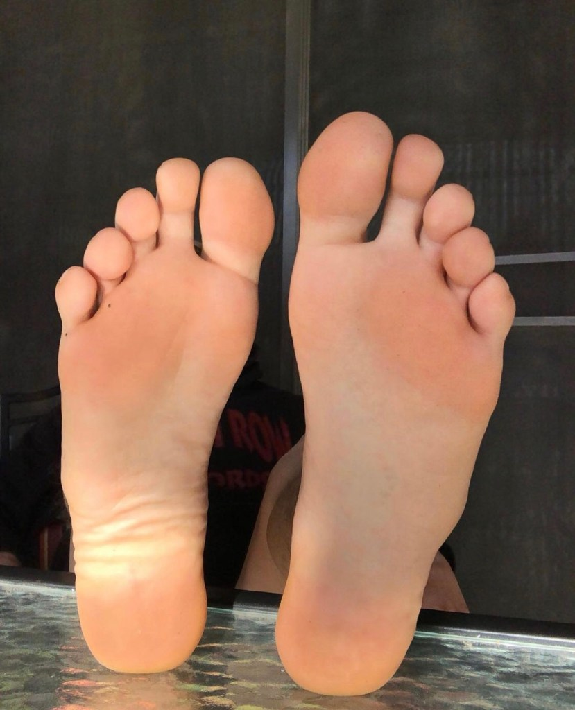 redfootzefff puts his bare soles up on the glass table