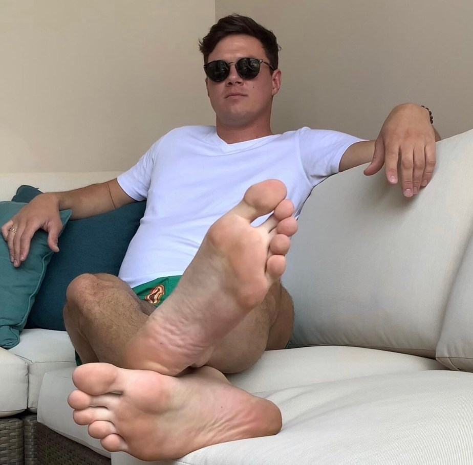md.hawk wearing sunglasses shows off his size 15 bare soles