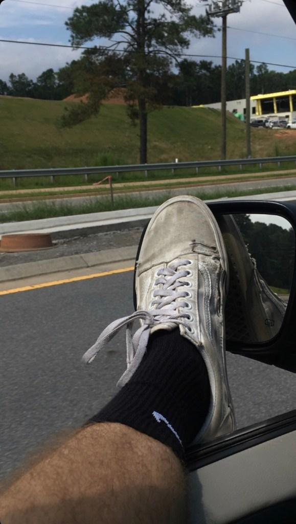 nike.bro2000's black Nike crew socked foot in Vans sneakers