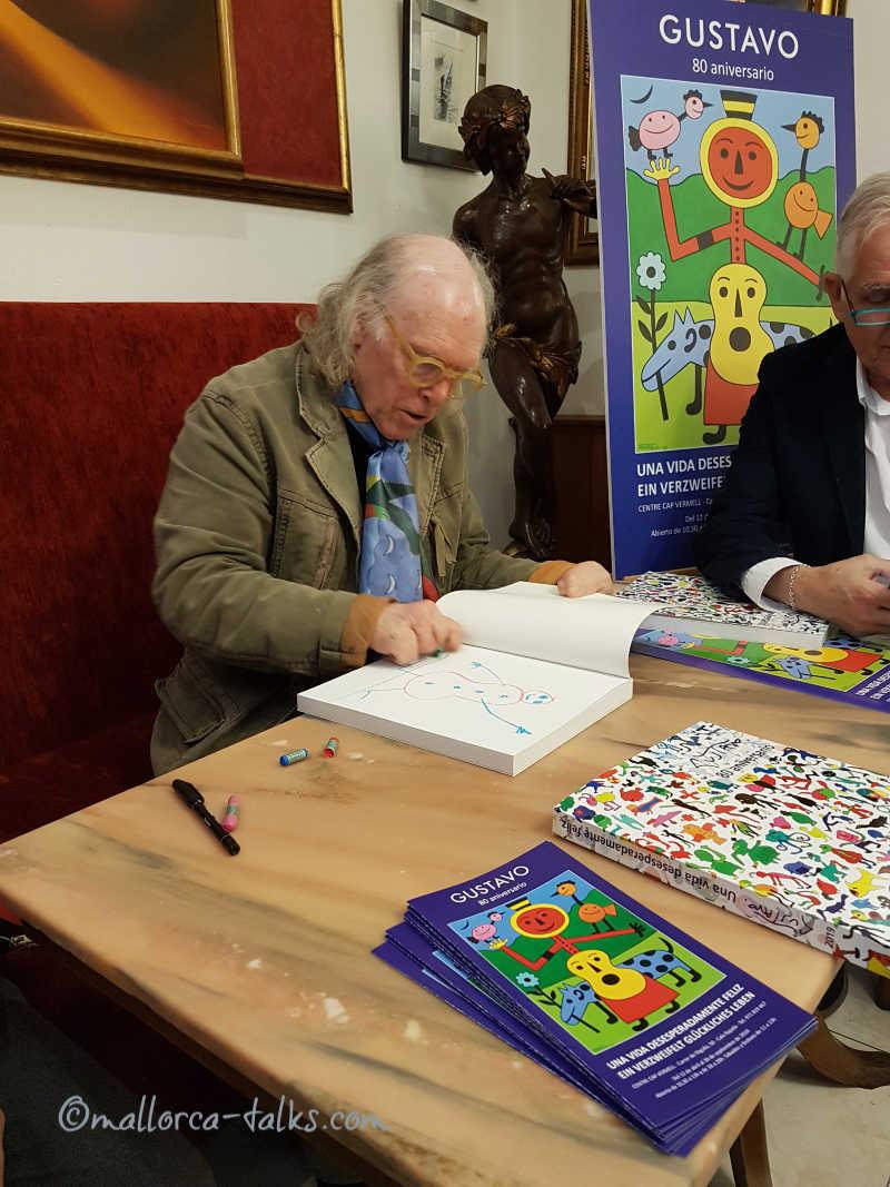 Künstler Gustavo signiert seinen Katalog