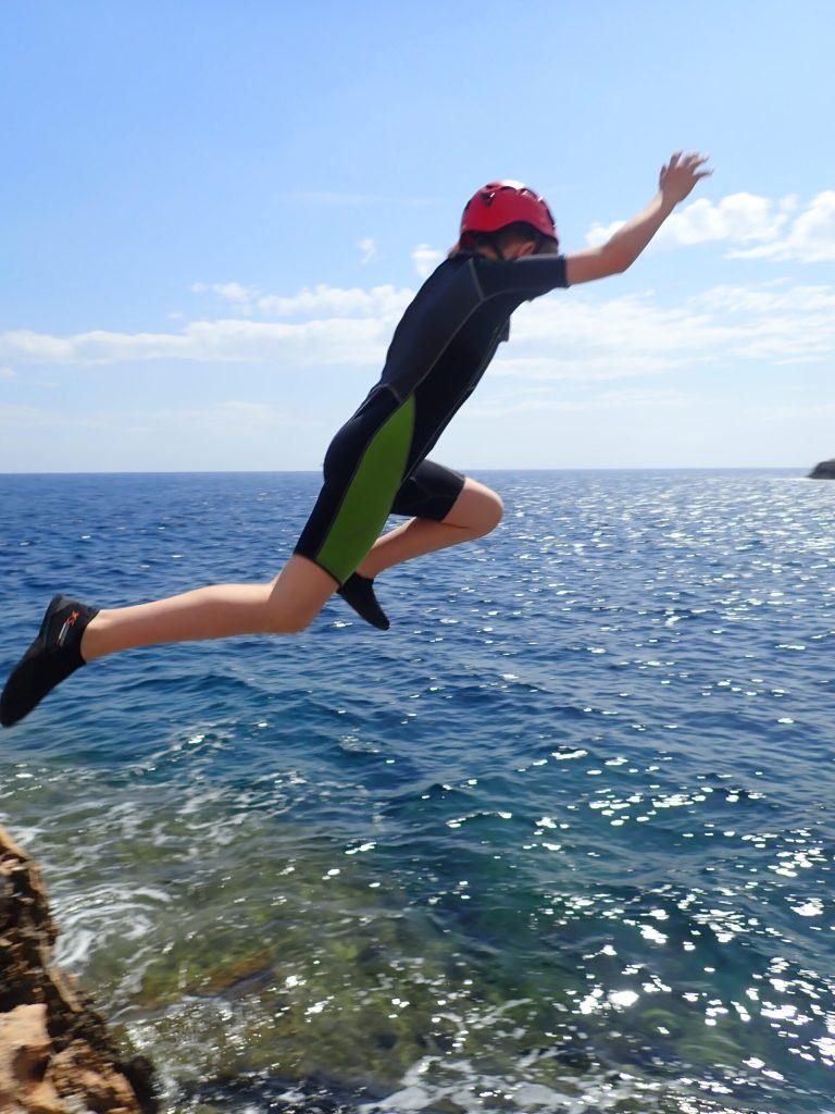 Kind springt von Klippe ins Wasser