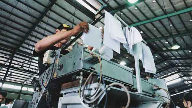 A worker operating a machine in a factory