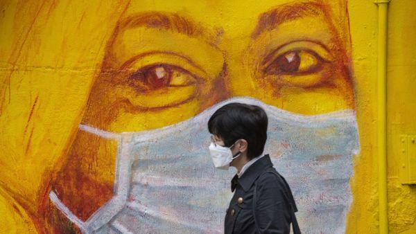 Una persona con una mascherina passa davanti a un murale che raffigura la stessa cosa nel distretto di Soho, a Hong Kong. Credit: Miguel Candela Poblacion : Anadolu Agency via Getty.