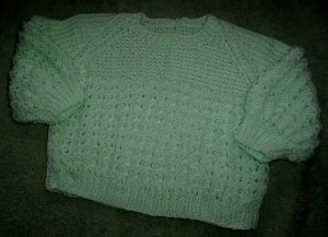 Light green knitted sweater for a baby