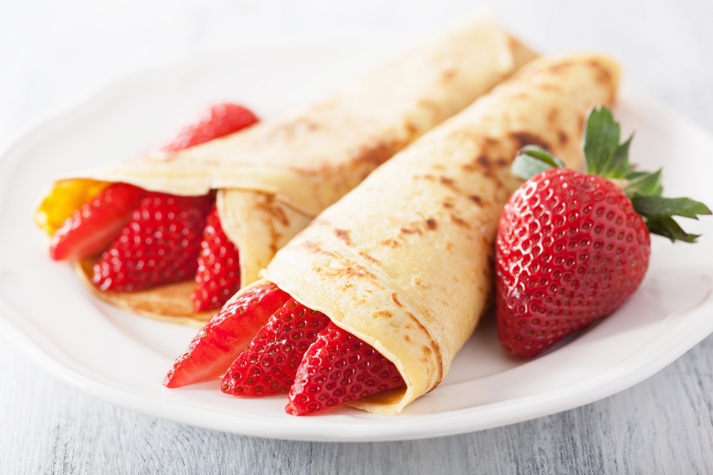 strawberries in a crepe on a white plate