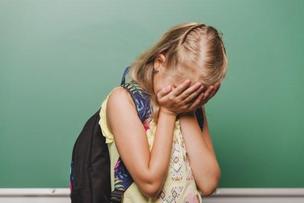 superproteção e negligência fatores que levam as crianças a fazerem bullying - criança com a mão no rosto