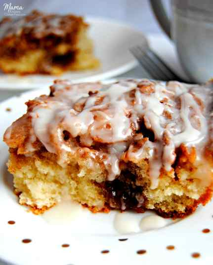 Gluten-Free Cinnamon Roll Cake slice on a white plate with a white coffee cup, fork and another cake slice in the background.