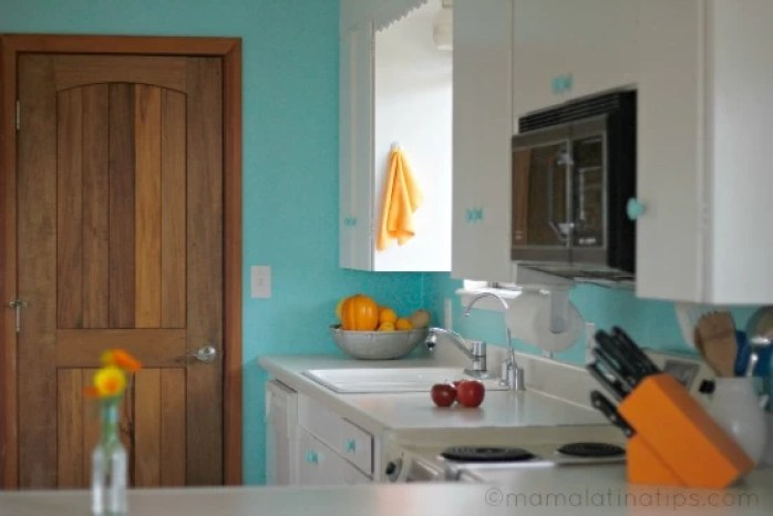 Same small kitchen with turquoise walls and a wooden door.