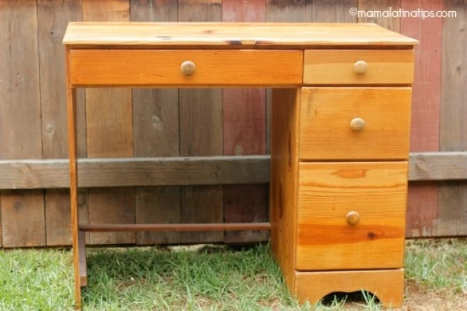 A small wooden desk with four drawers