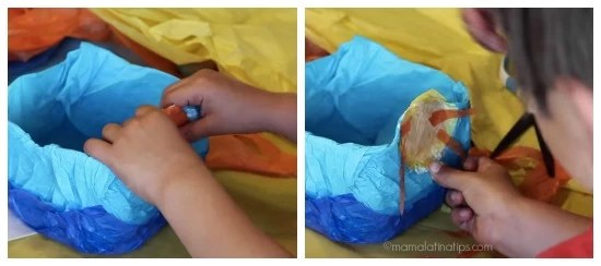 Kid adding a sun of tissue paper to a milk jug - mamalatinatips.com