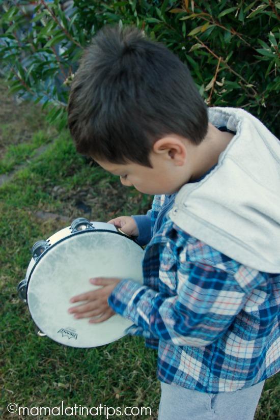 Kid playing a tambourine - mamalatinatips.com