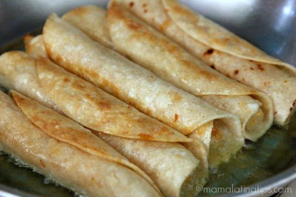 Potato flautas frying by mamalatinatips.com